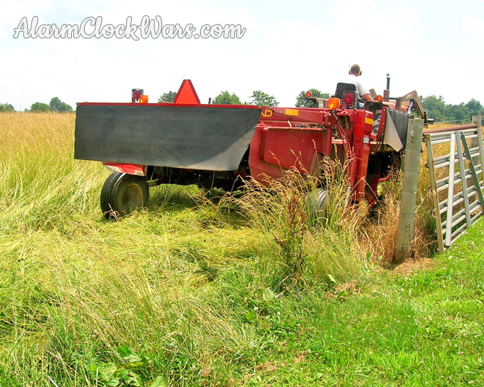 The back of the mower-conditioner cutting hay.