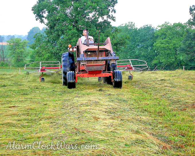The hay tedder is pulled behind the tractor.